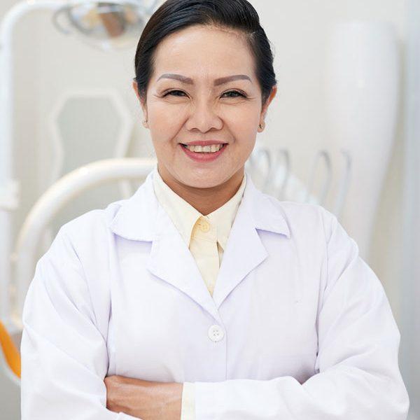 cheerful-ethnic-dentist-in-white-gown-NX8F3SB.jpg